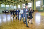 Przedstawiciele klas pierwszychudają się pod popiersie Stanisława Staszica